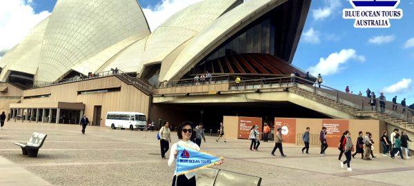 Hướng dẫn viên Blue Ocean Tours chụp ảnh phía bên ngoài Nhà hát Cánh Buồm (Sydney Opera House)